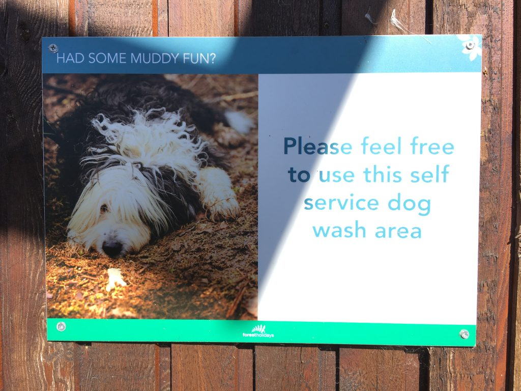 Sign of self service dog wash area on a wall at Forest Holidays