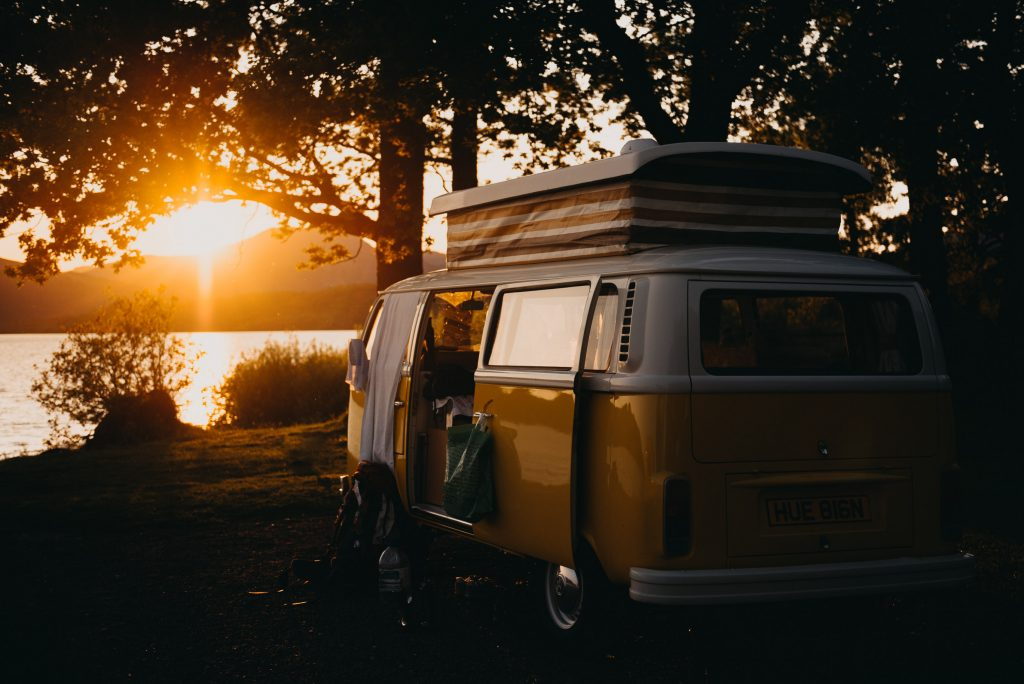 Retro campervan at sunset near body of water