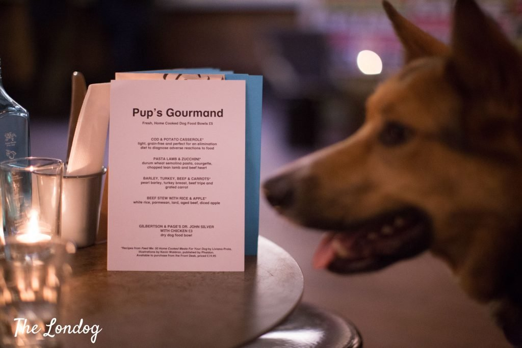 Pup's Gourmand Menu on a table, with dog on the side waiting
