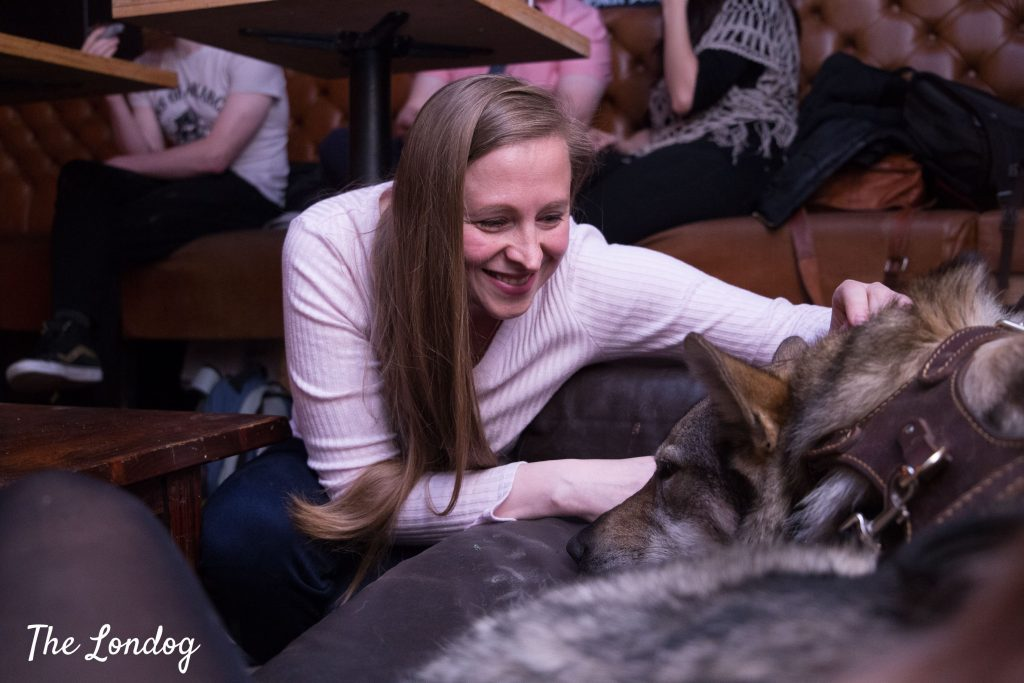 Actress pets large dog on sofa at the end of dog-friendly theatre performance