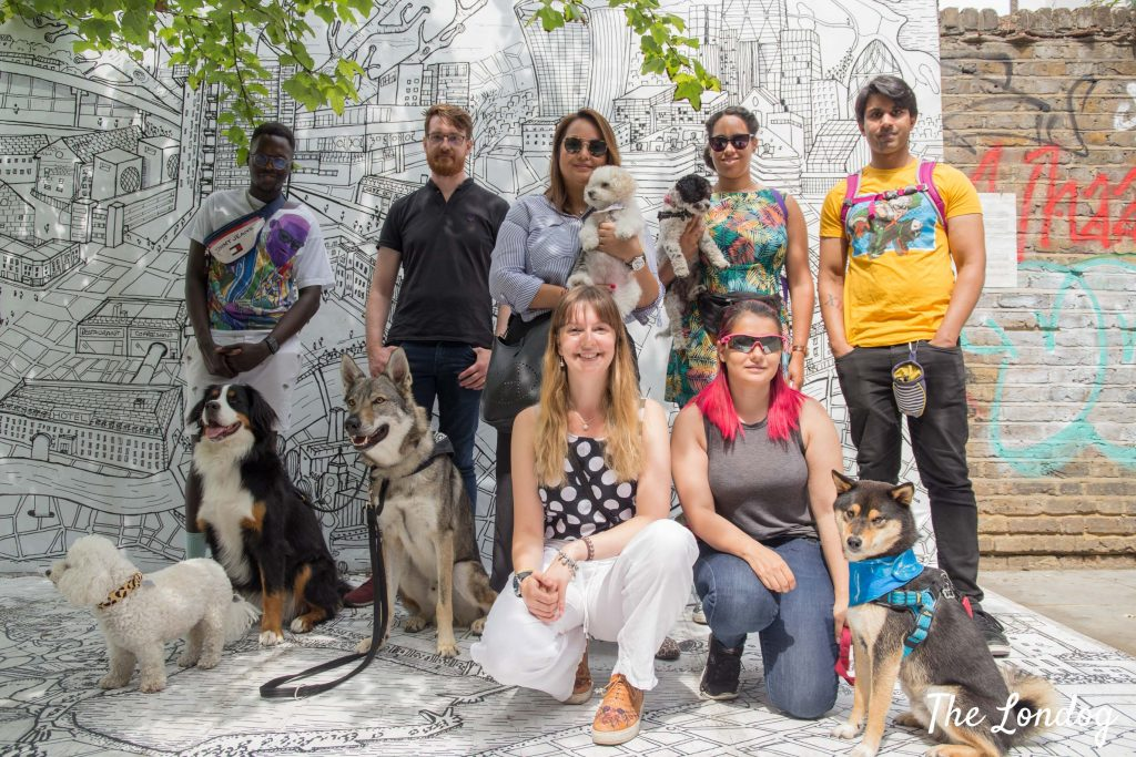 Group photo in front of street art in Notting Hill with dogs